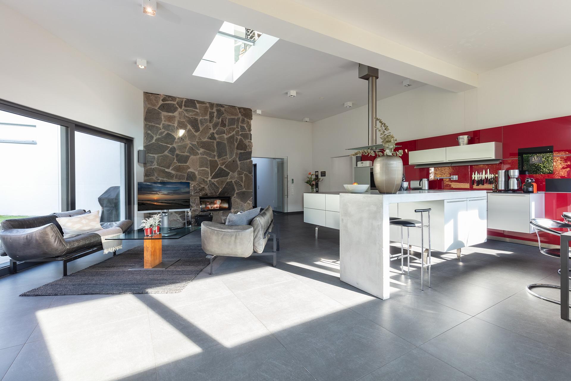 Moderne Wohnküche mit großer Kochinsel und bodentiefen Fenstern und Zugang zum Garten.