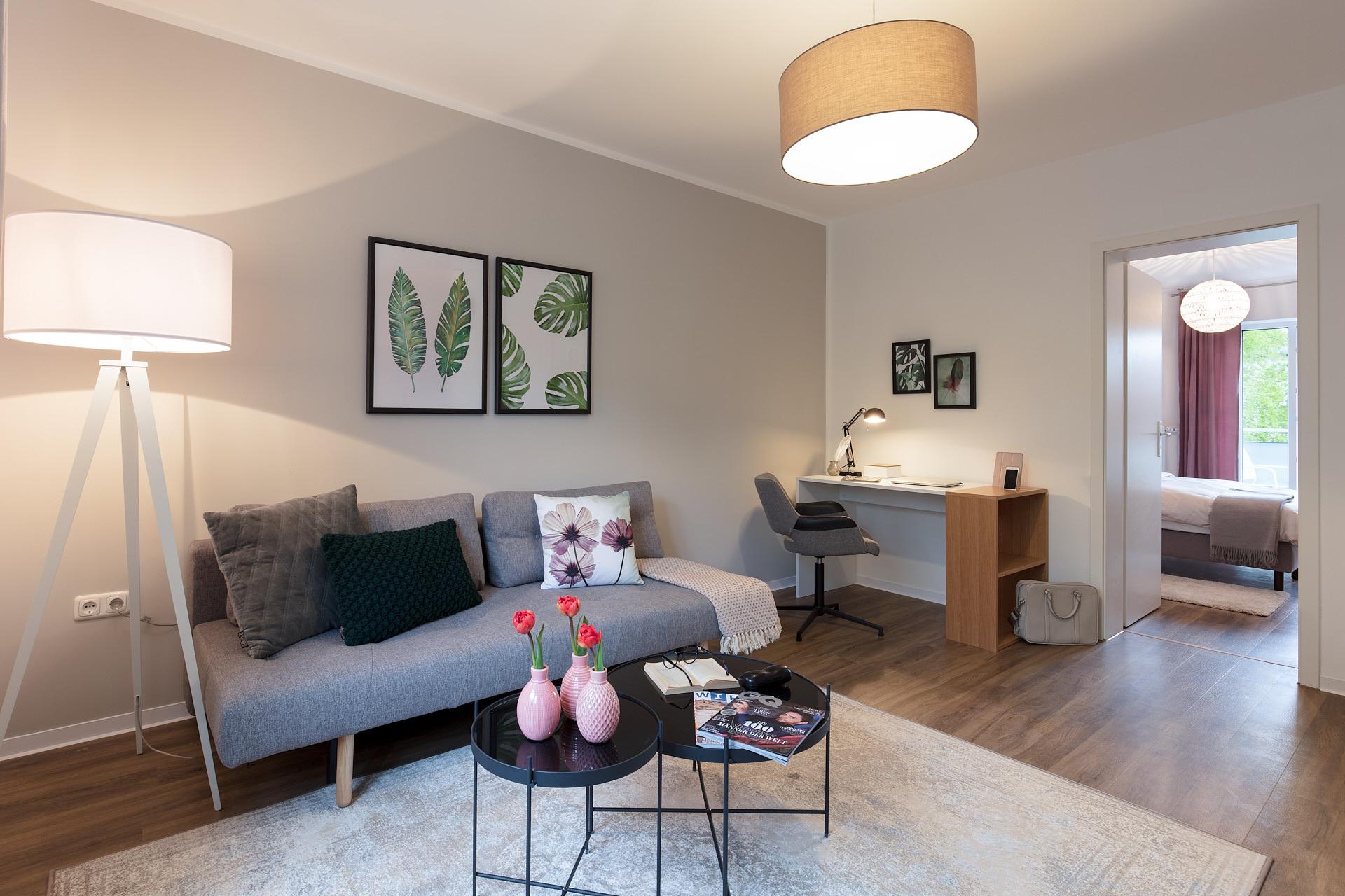 Gemütlicher Wohnbereich eines kleinen Apartments mit separatem Arbeitsbereich.