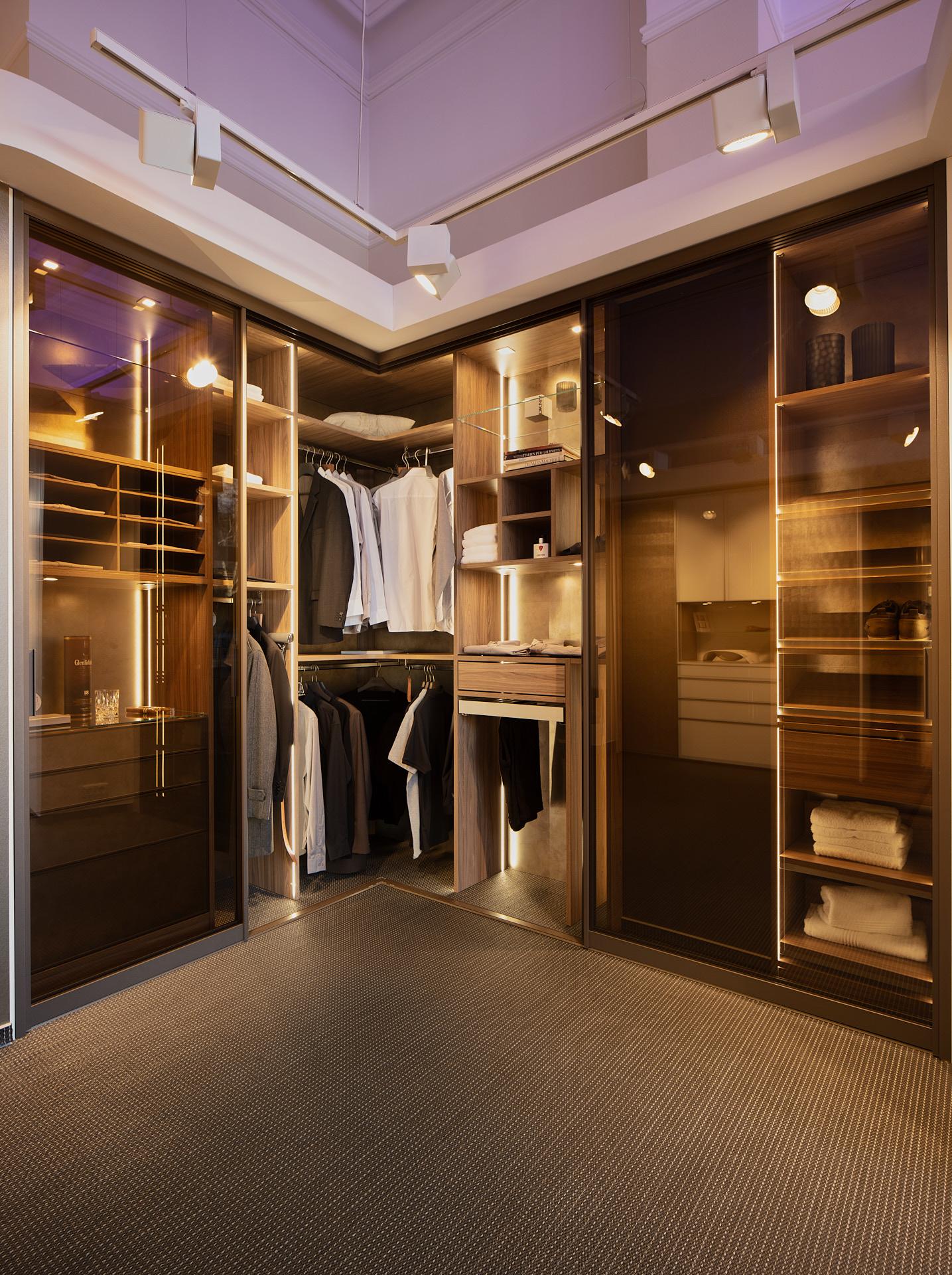 Maßgefertigter deckenhoher Eck-Kleiderschrank mit Schiebetüren aus Glas.