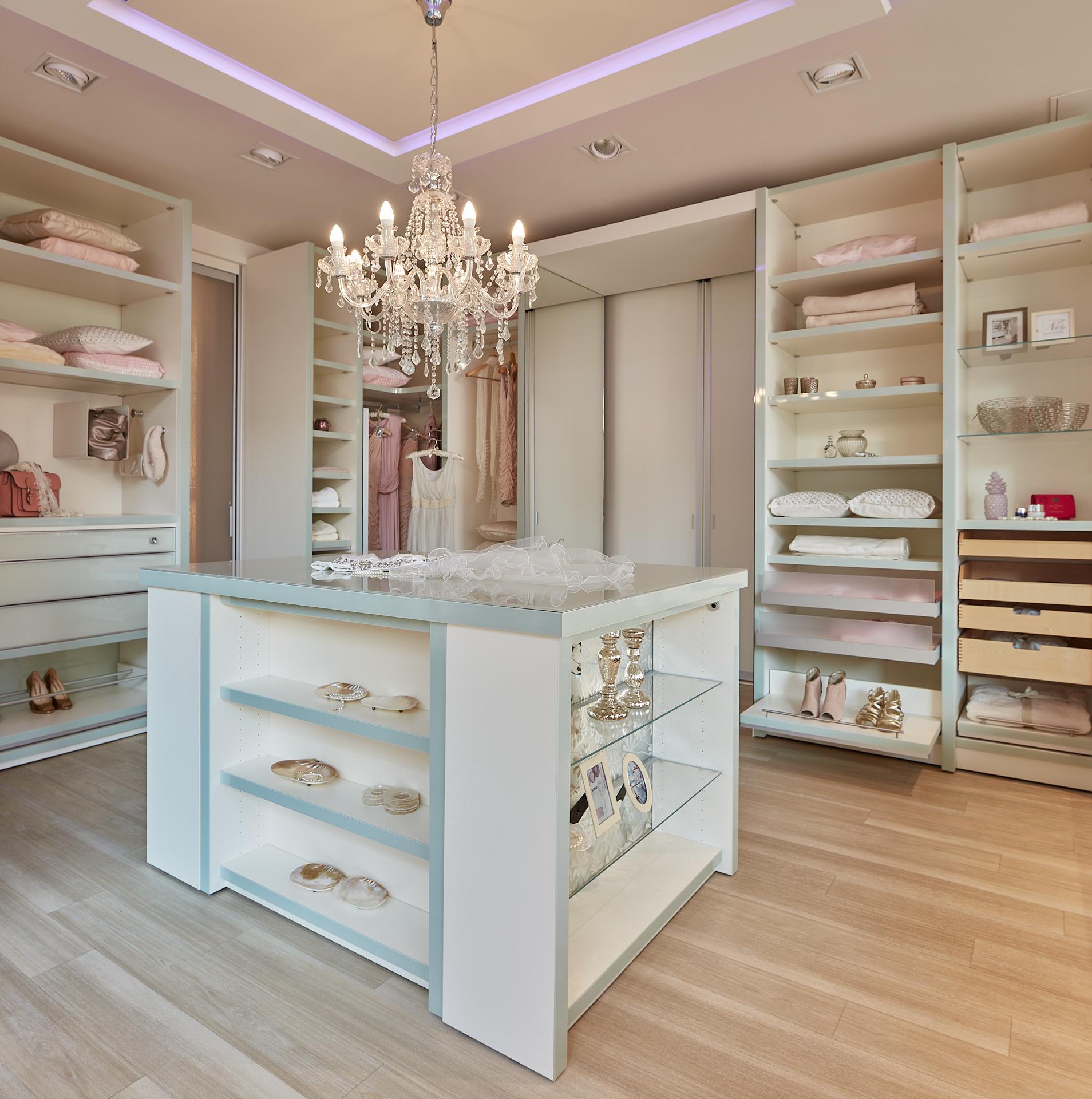 Luxus Ankleidezimmer mit Mittelblock und elektrischen Schiebetüren.
