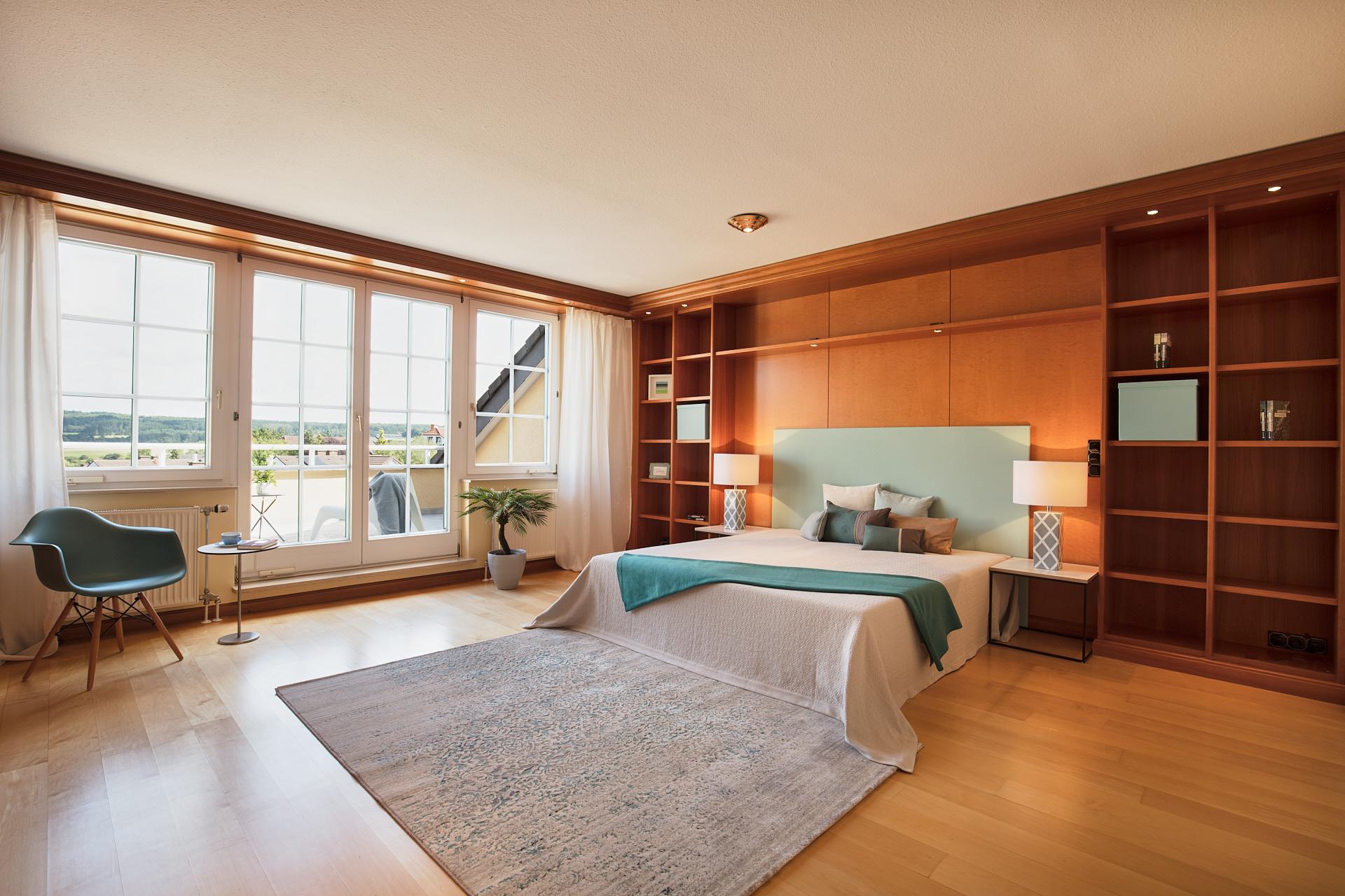 Großes Schlafzimmer mit umlaufenden Einbauschränken aus massivem Holz und Doppelbett.