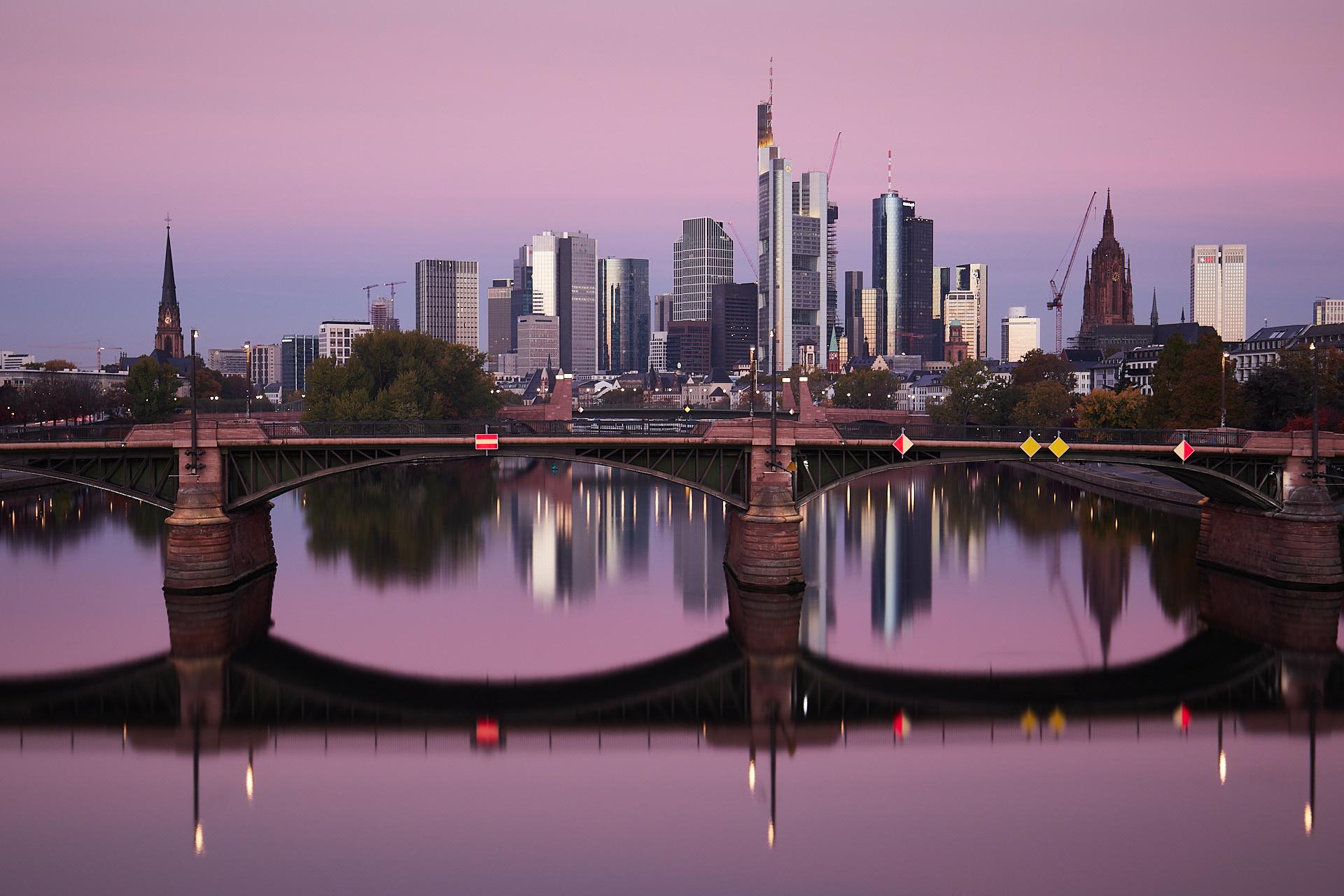 Blick über die Alte Brücke auf die Frankfurter Skyline bei Sonnenaufgang